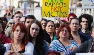 Women during an anti-rape protest display a sign saying 'blame rapists not victims'