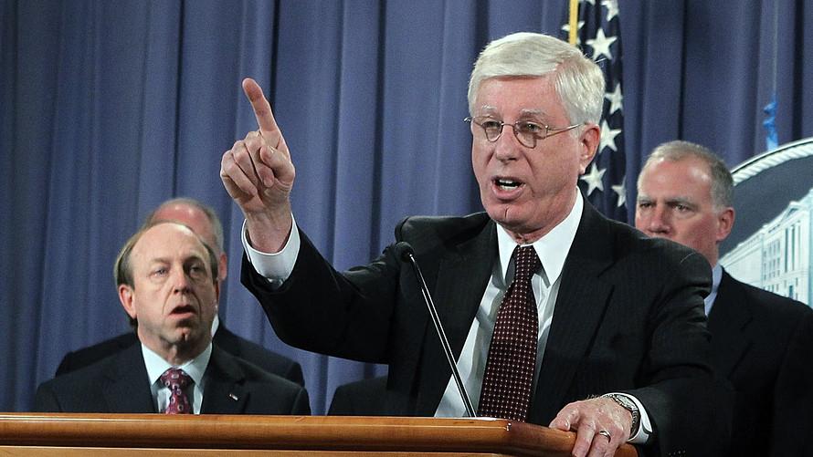 Iowa Attorney General Tom Miller speaking at a podium.
