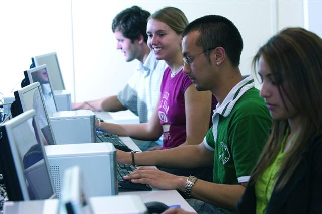 Students working together on computers in a computer lab.
