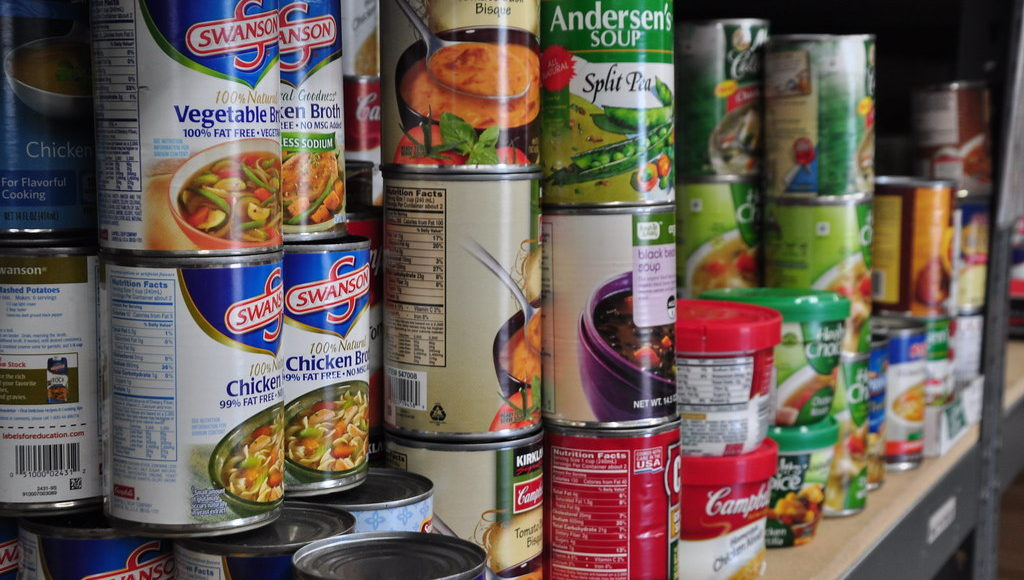 A collection of canned food items in a pantry.