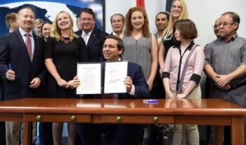 Florida Governor Ron DeSantis signing a bill.