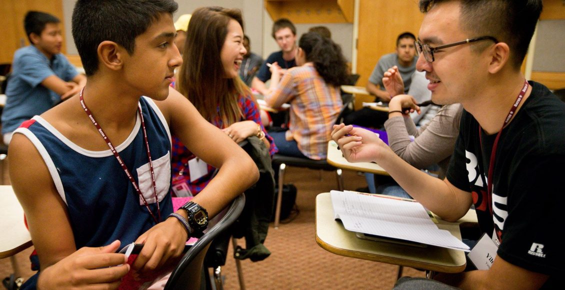 Students talking in a classroom.