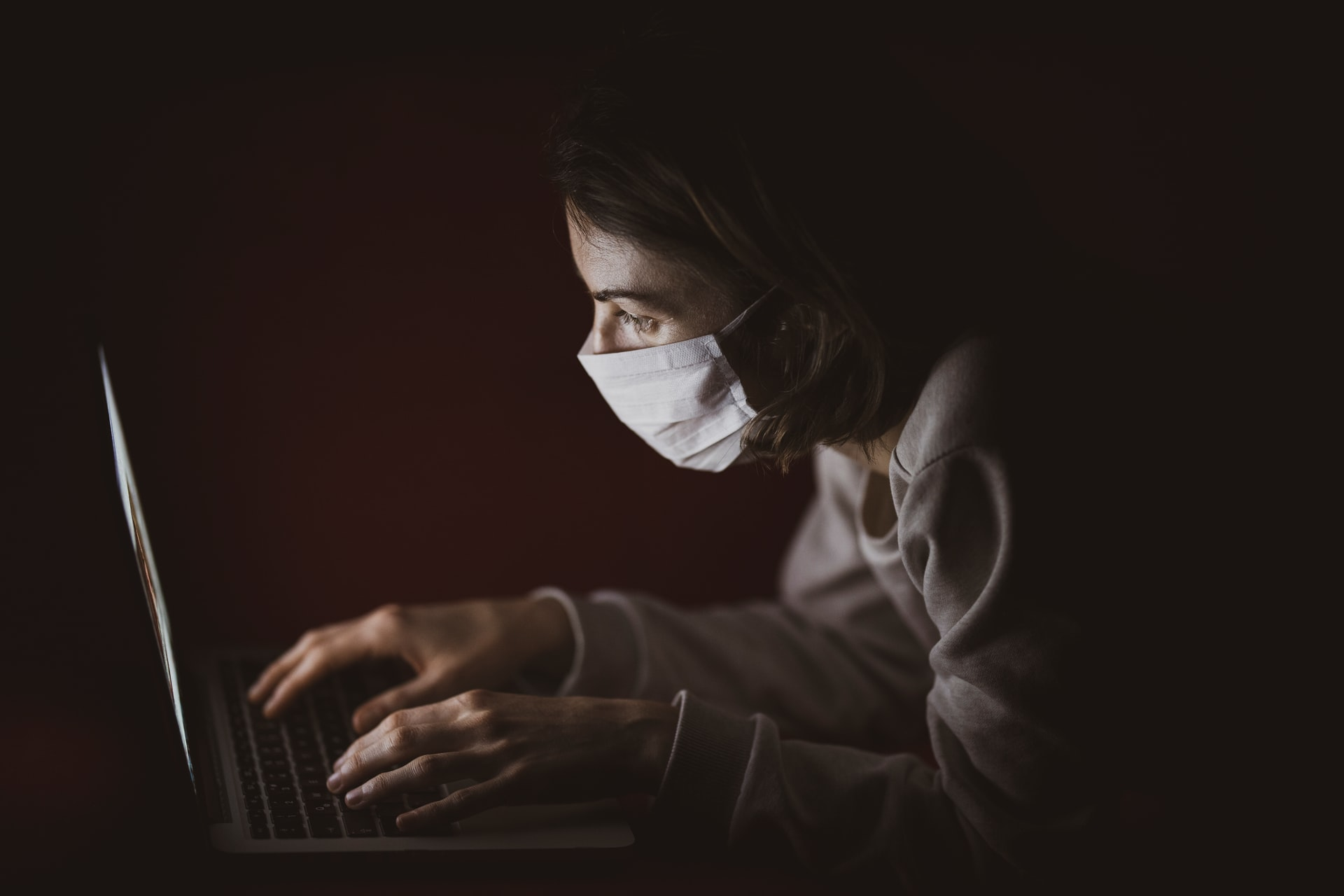Person with masks in front of laptop