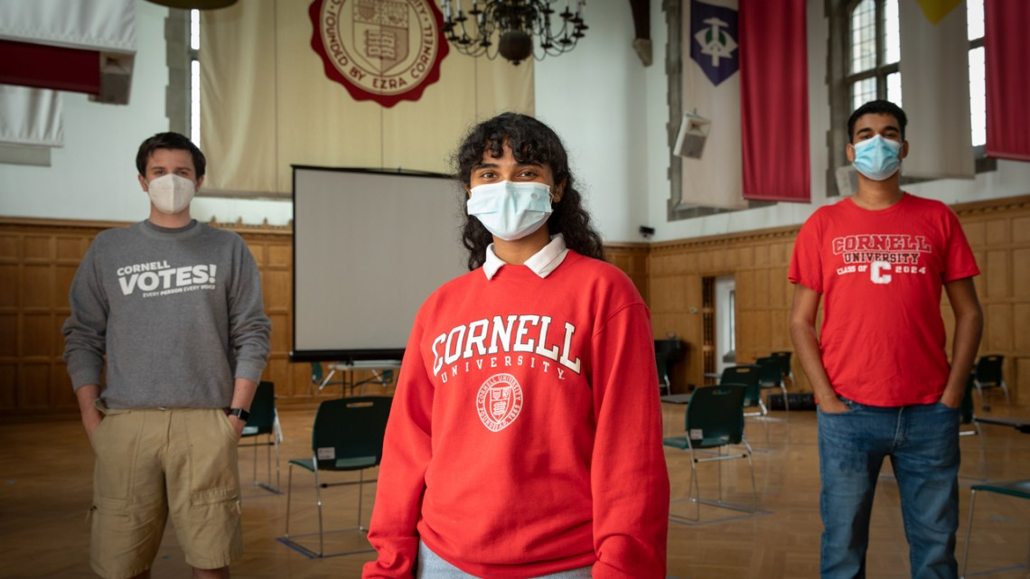 Three socially-distanced and masked students from Cornell Votes
