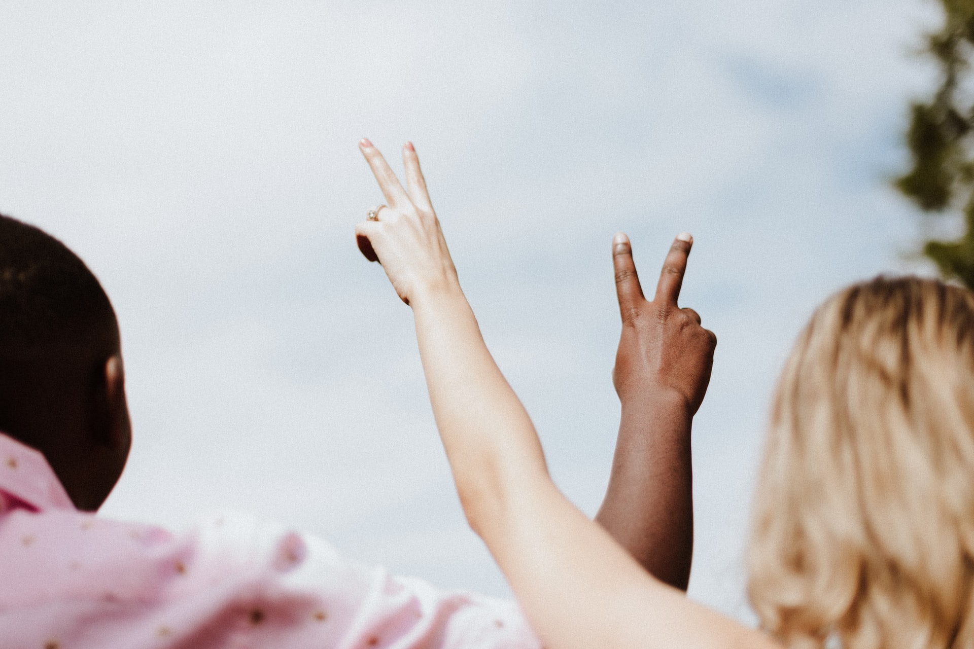 Photo of a Black and a white person making the peace sign