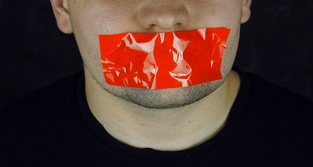 Photo of man with red tape across his mouth