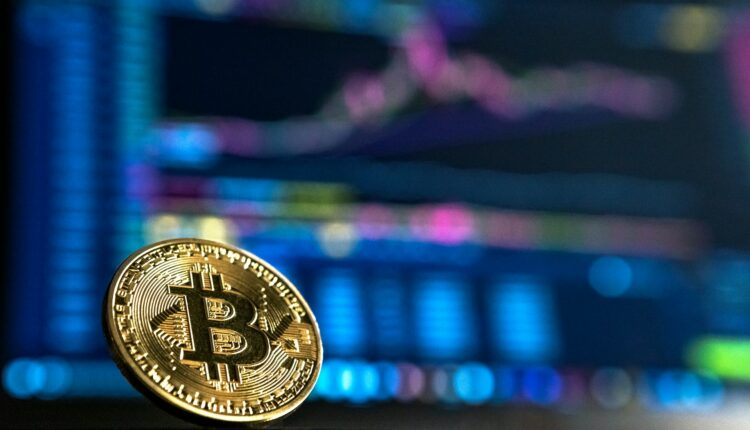 Photo of a bitcoin with a computer in the background