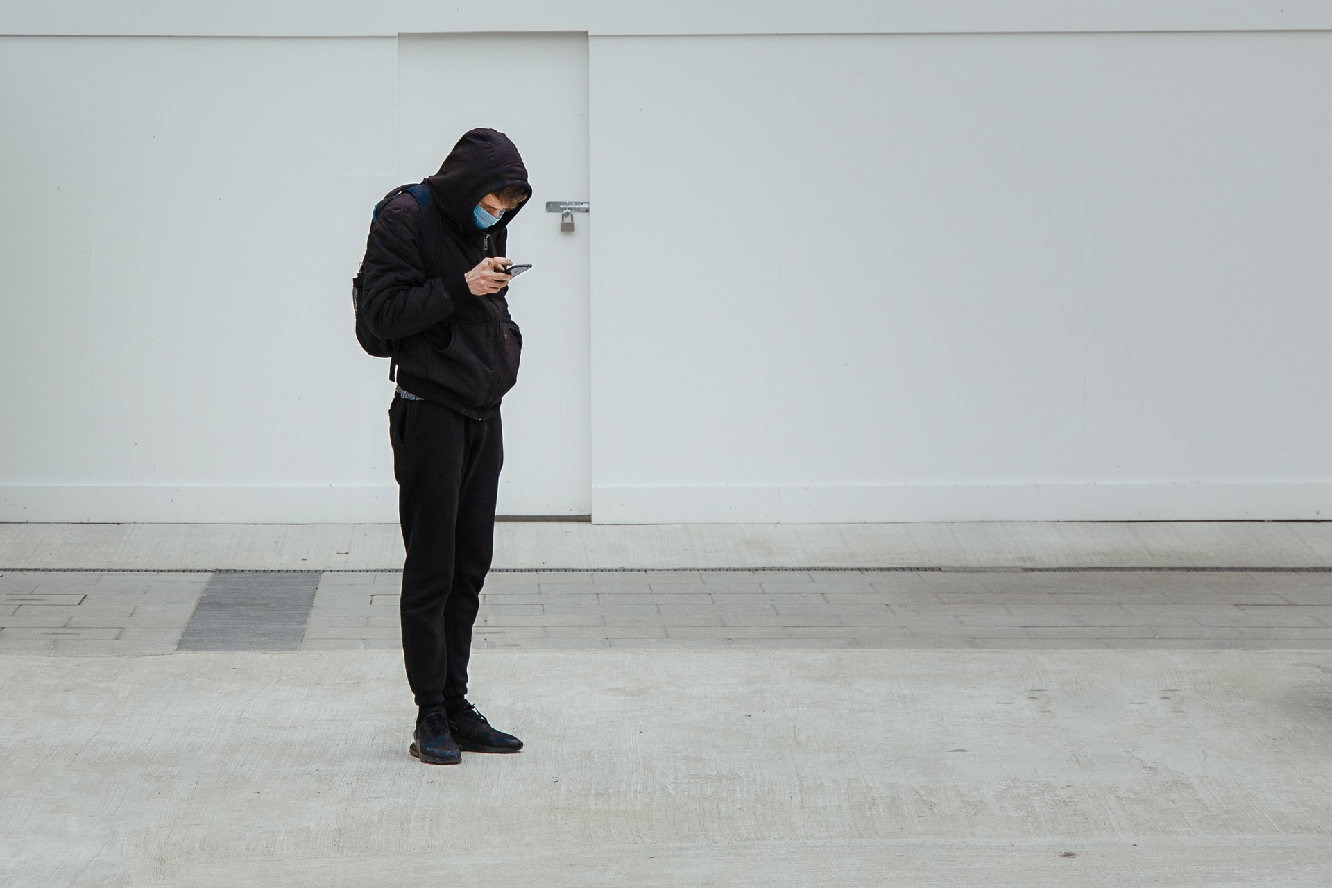 Photo of a student with a mask looking at his phone.