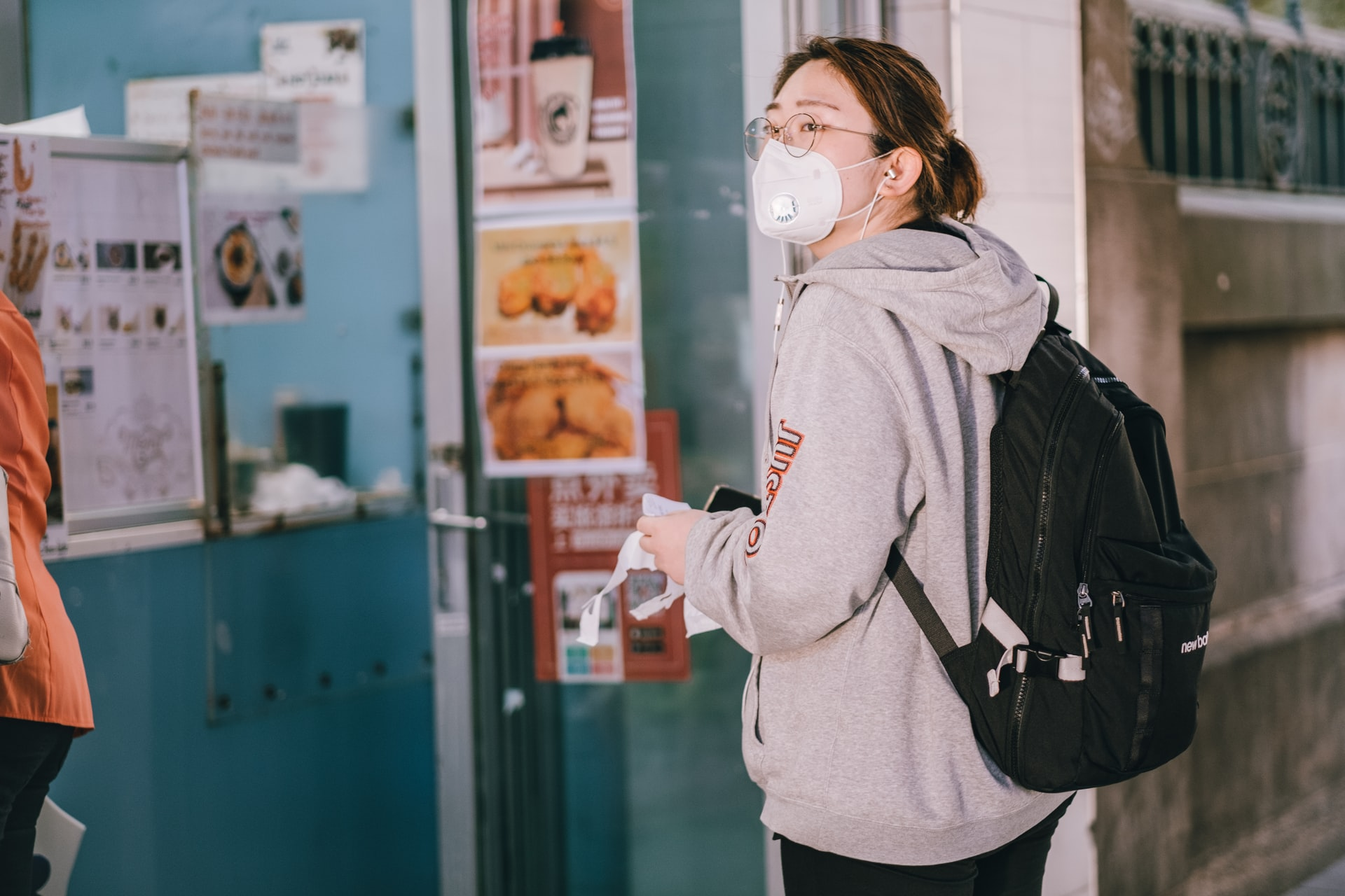 Photo of a woman in face mask waiting in a line to get takeaway food during the coronavirus pandemic