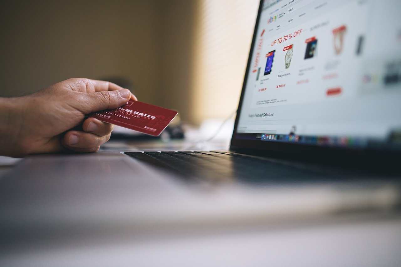 A photo of a person referring to their credit card for an online purchase.