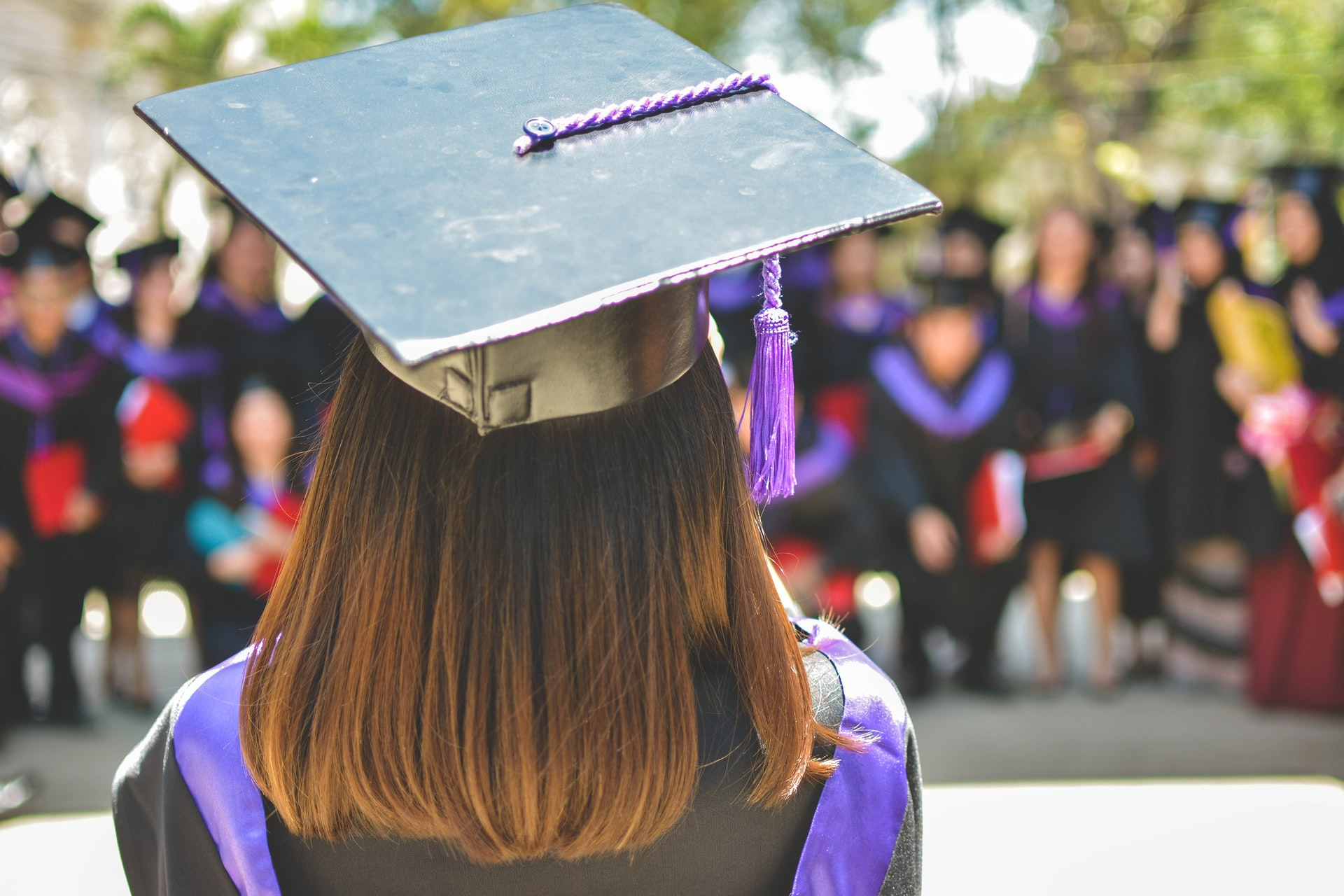 Back angle shot of a female graduate wearing a graduation cap and toga
