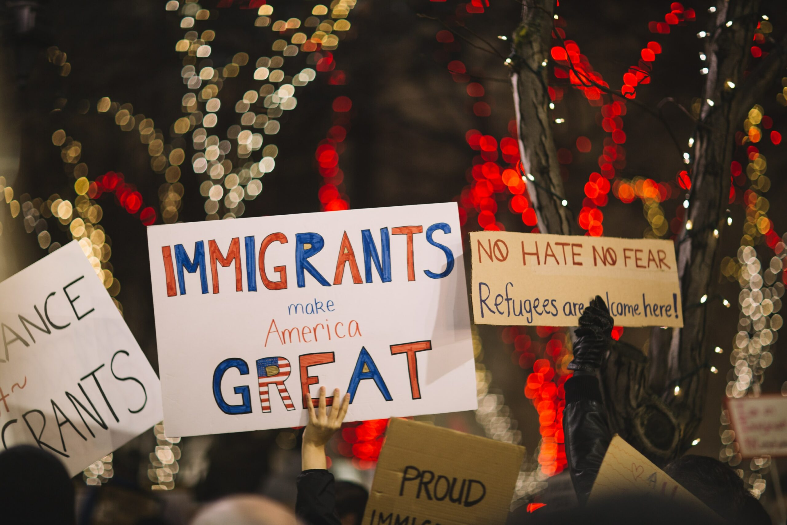 """Protestors with signs reading """"Immigrants make America Great"""""""