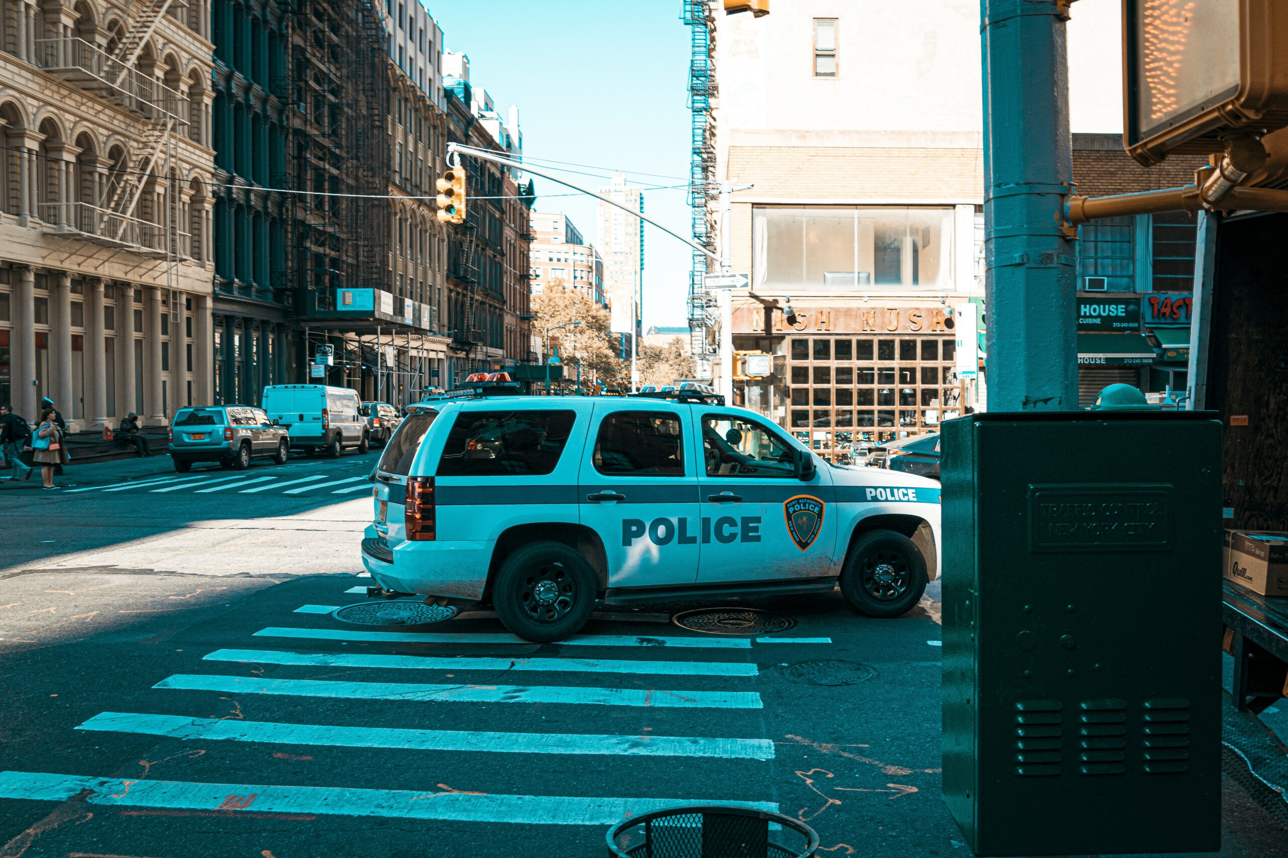 A police car parked haphazardly on top of a pedestrian crossing.