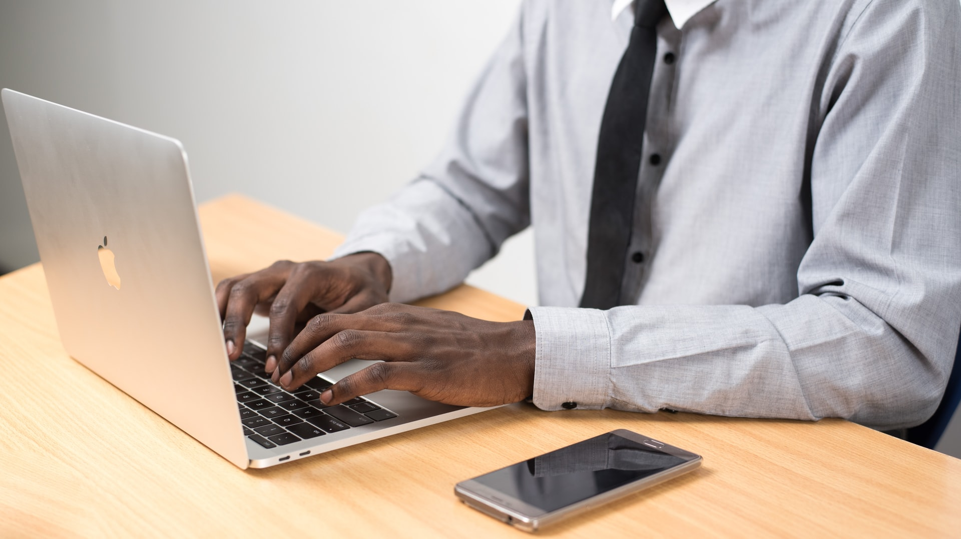 Photo of a man sitting behind a laptop