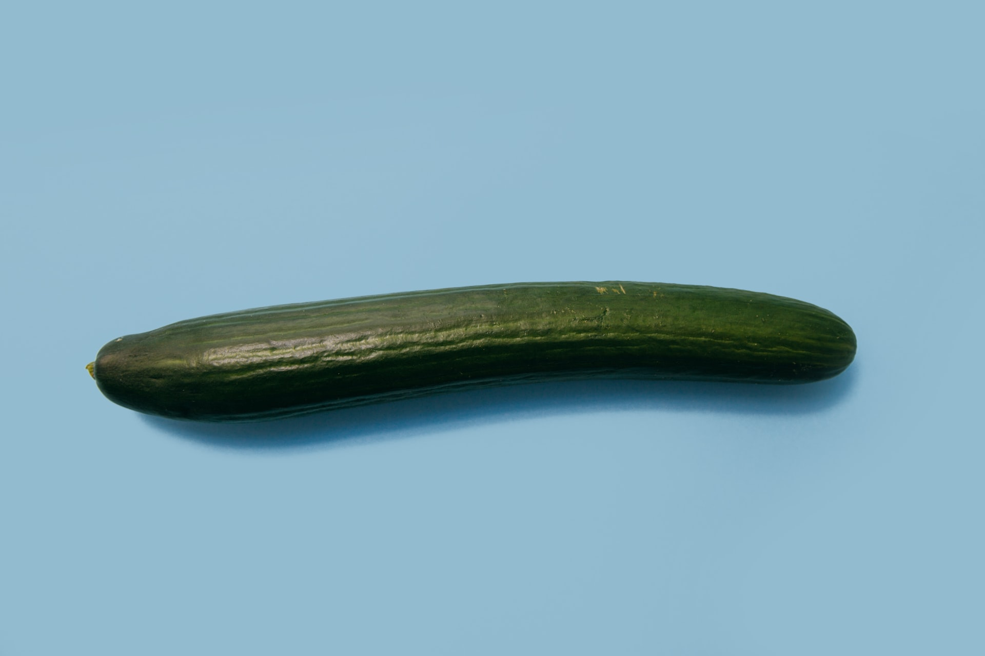 A picture of a cucumber on a blue background