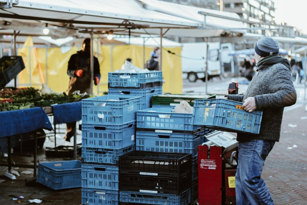 Photo of man carrying crates