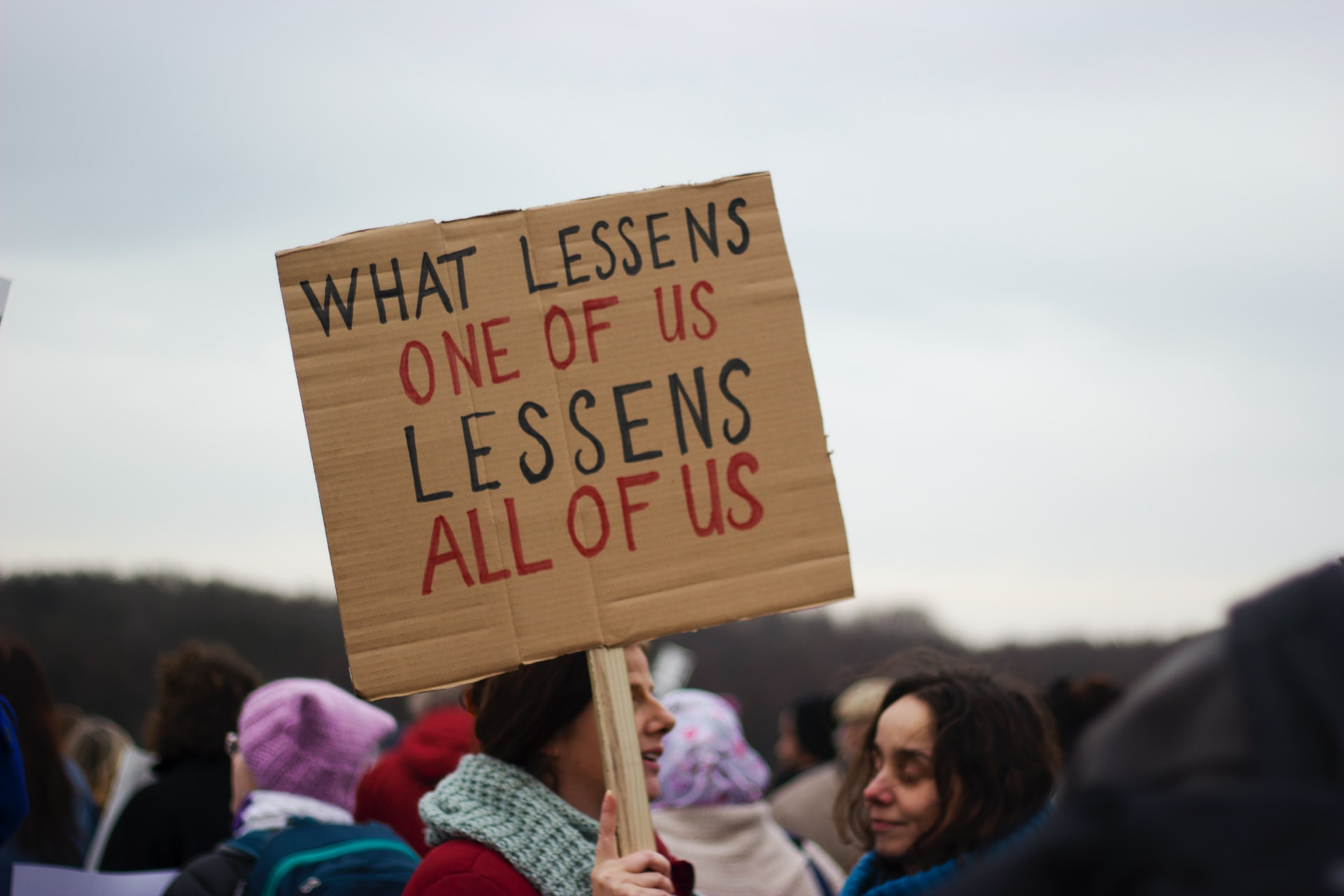 women holding protest sign about equality