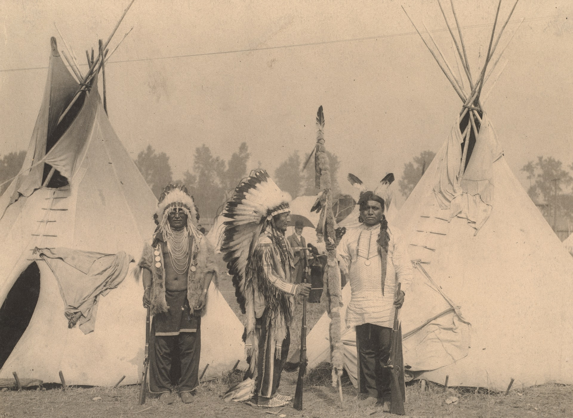 Three members of the Sioux tribe pose in Indian Village, 1898.