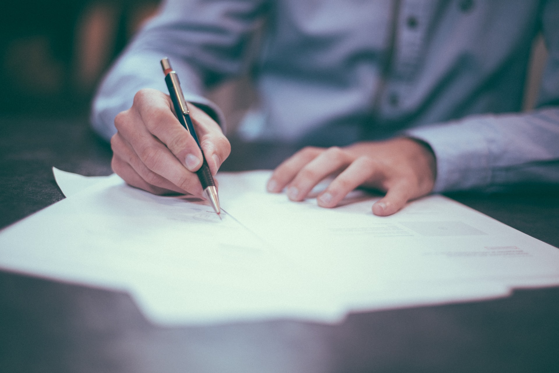 Man writing or signing a document.
