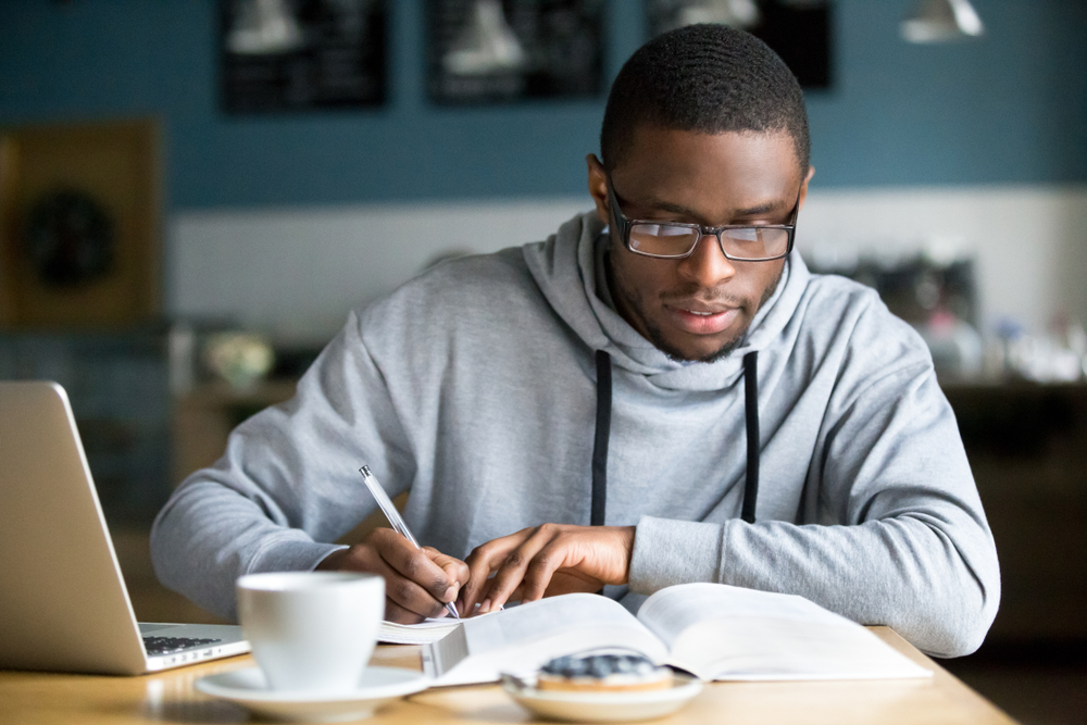 African American student in glasses making notes while studying