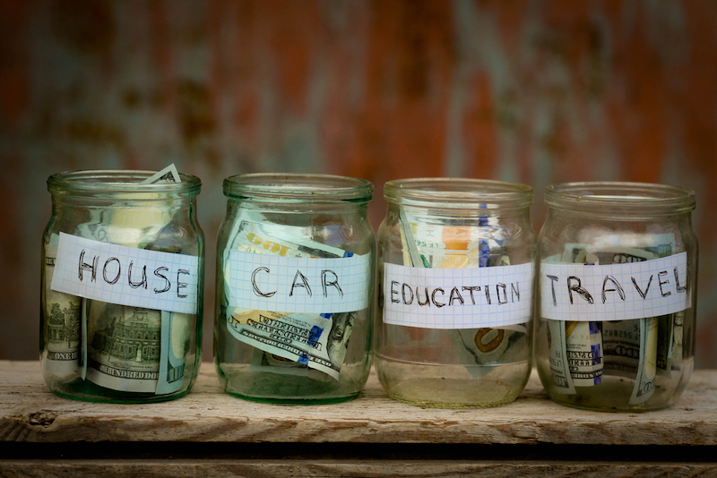 Glass jars with dollars and text: house,car, travel, education