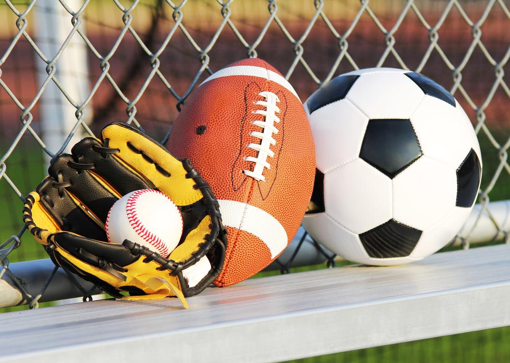 Soccer ball, american football and baseball in yellow glove