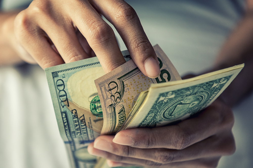 Close-up of hands counting American dollars