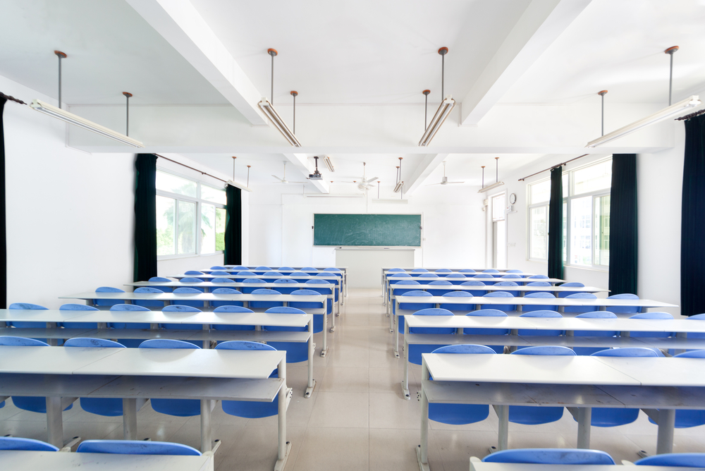 Bright empty classroom with desks and chairs