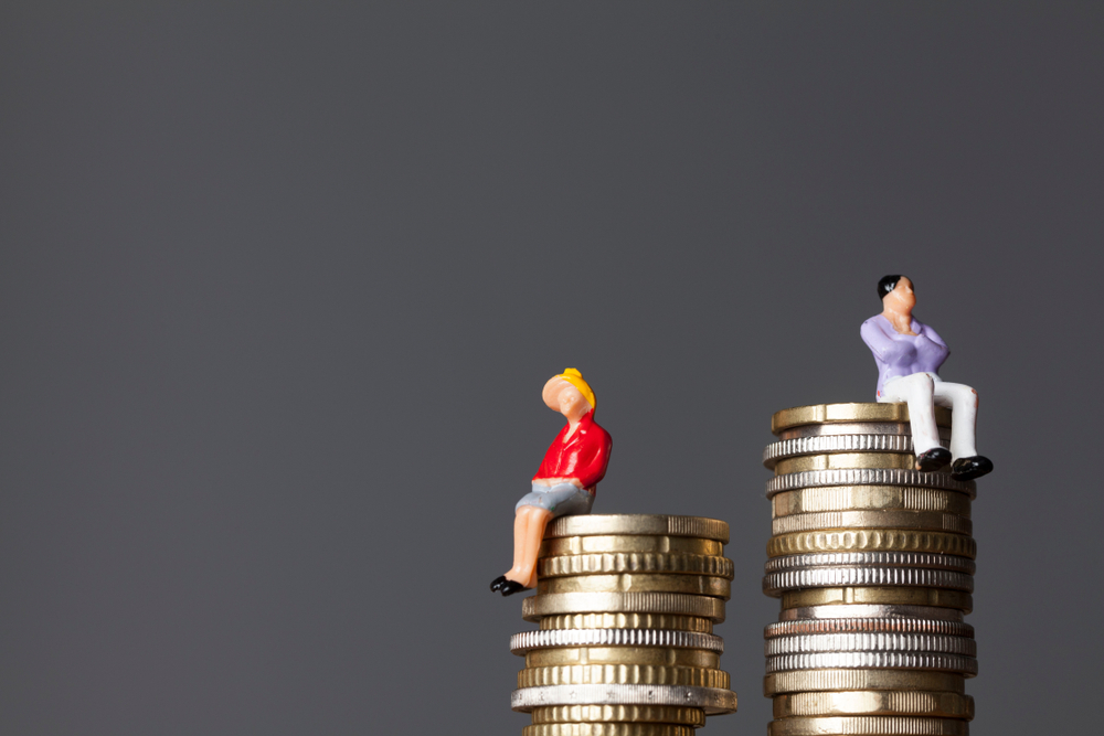 Man and woman on a stack of coins, gender pay equality concept