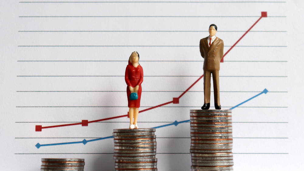 Miniature people standing on a pile of coins in front of a graph, representing the gender pay gap in profession
