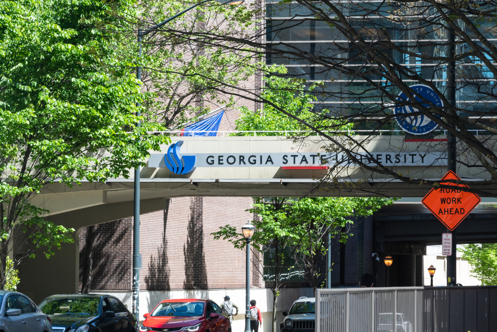 Georgia State University urban city campus with building hall sign and students walking