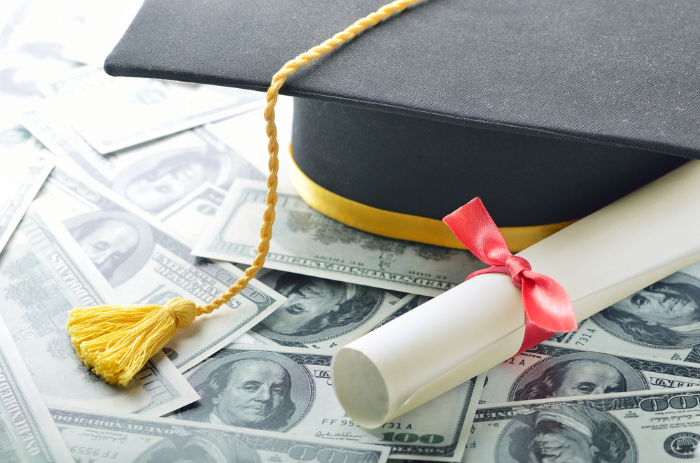 Graduation hat with college diploma and money