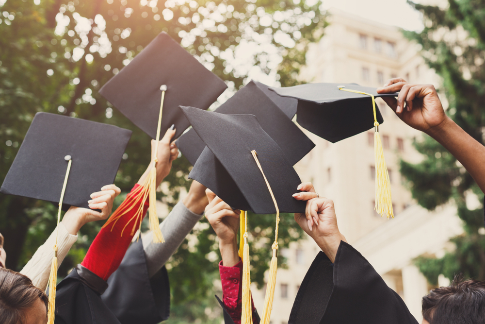 Group of students celebrating their graduation by throwing caps in the air