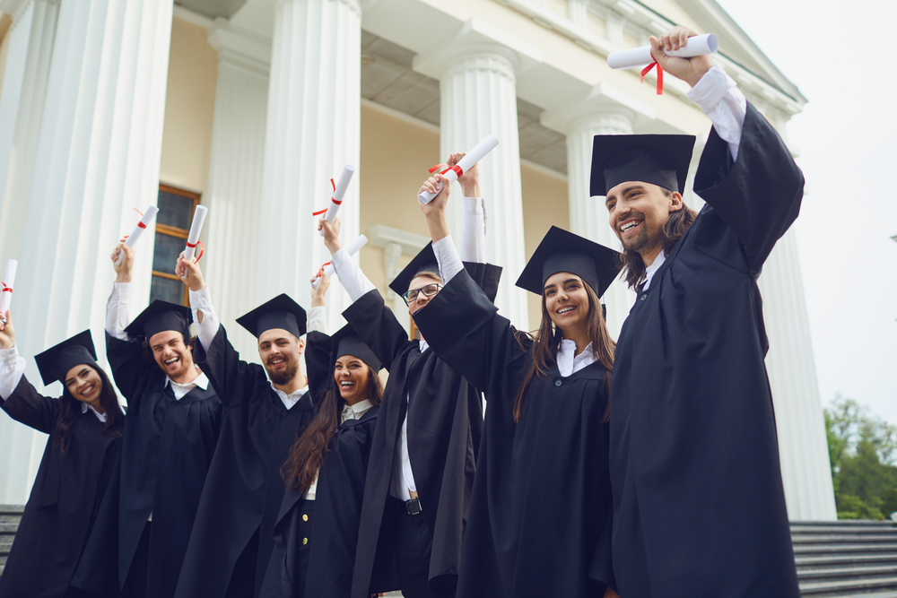 A group of graduate students raised their hands with diplomas up