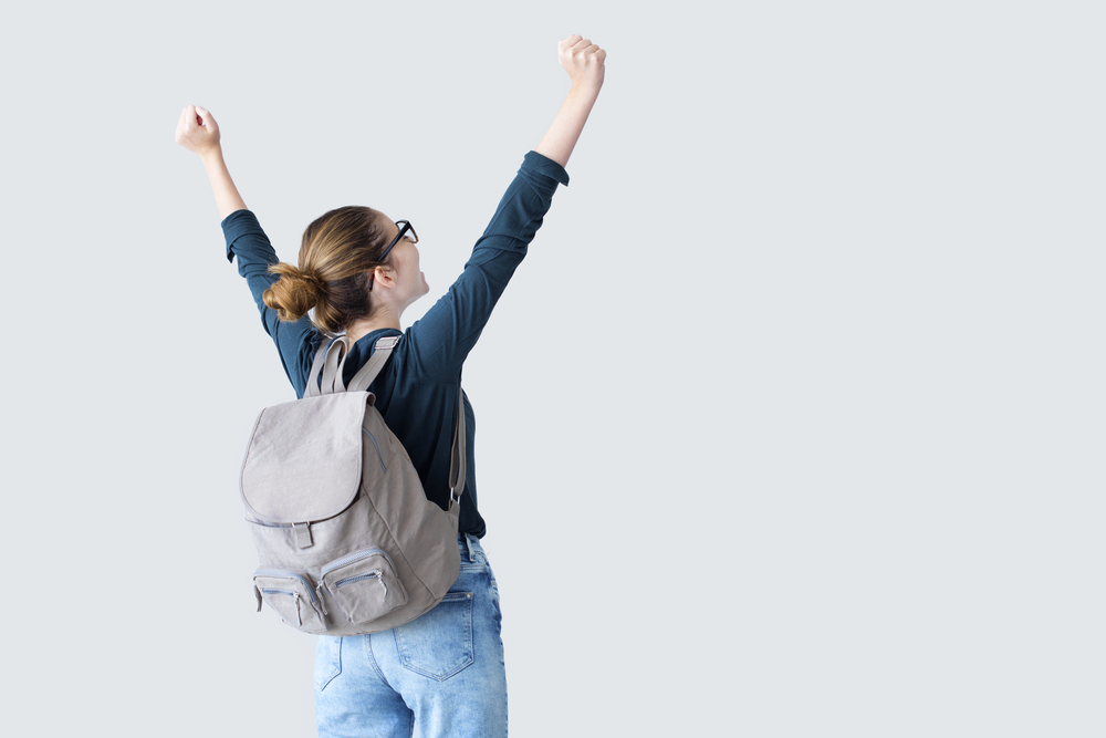 Happy student with arms raised on air