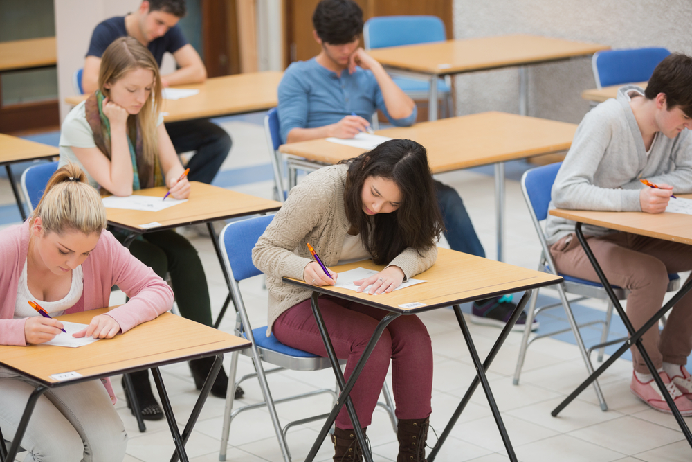 Students taking test in the exam hall of the college