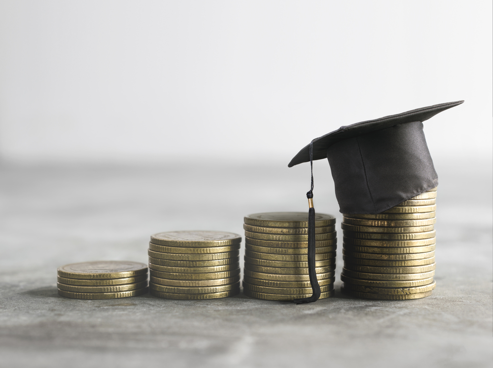 Graduate cap on top of the money, scholarship money, cost of education (tuition) and student loan debt concept.