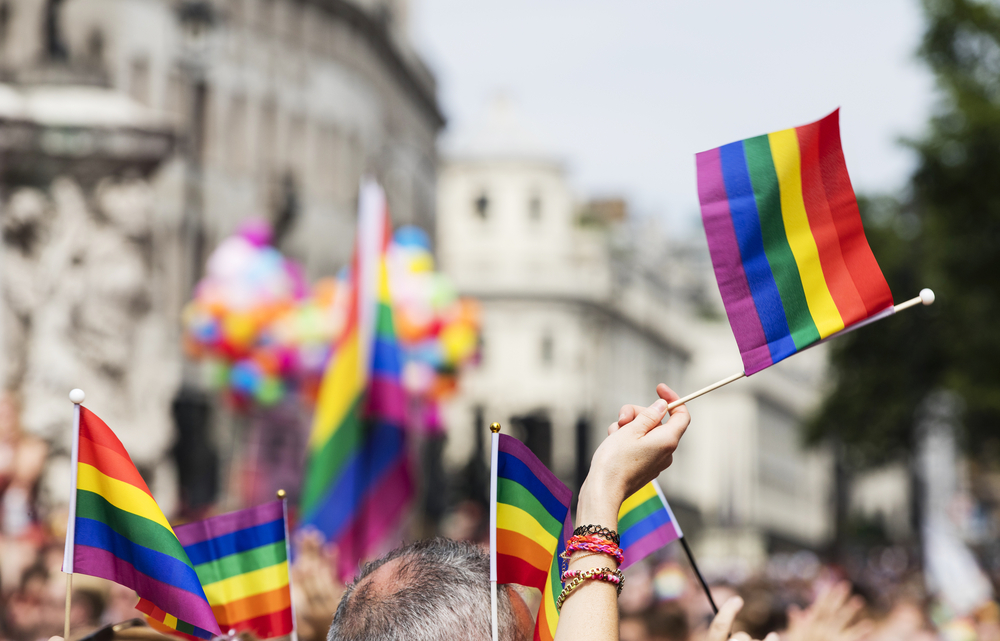 Spectator waves a gay rainbow flag at an LGBT gay pride march