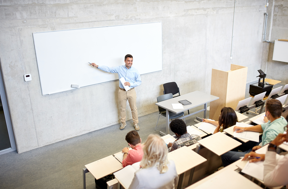Teacher with marker standing at a white board during a college lecture