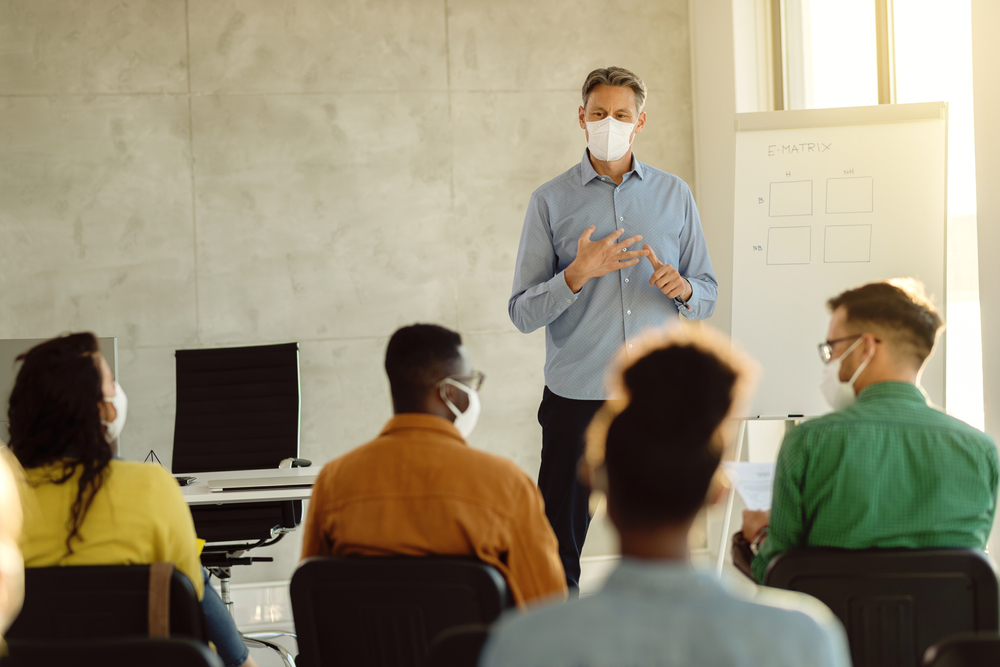 University professor wearing protective face mask while holding a class to group of students during coronavirus pandemic