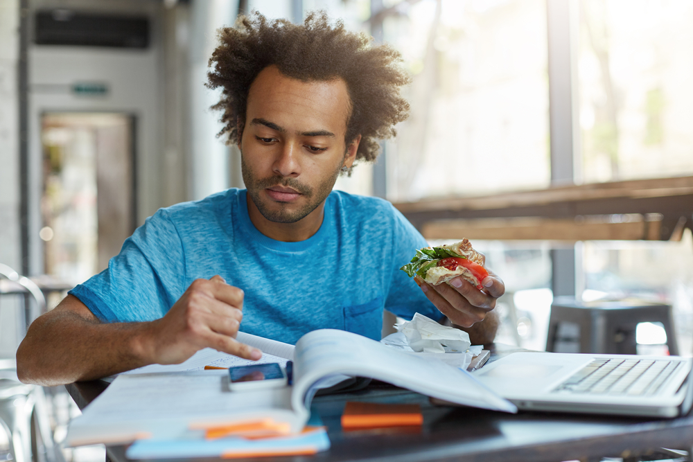 Black student with bushy hair looking in his smart phone while eating sandwich and resting after preparation for classes