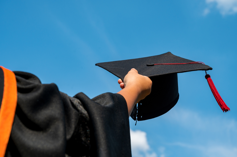 The students holding a graduation cap by their hand in a bright sky during a ceremony at the university