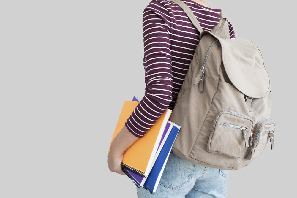 Student with backpack on gray background