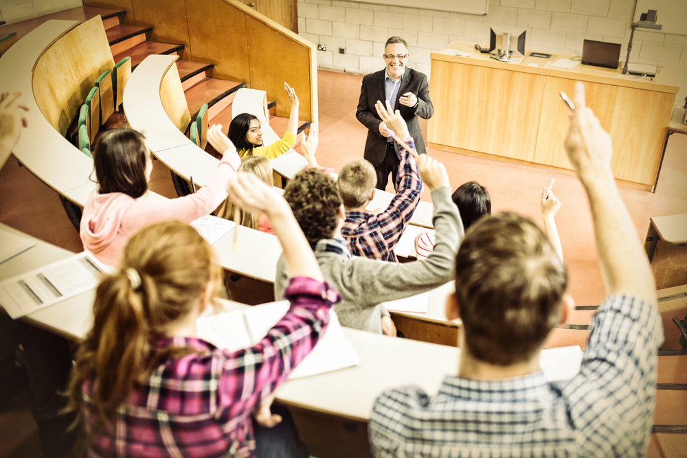 Rear view of students raising hands with teacher in college lecture hall