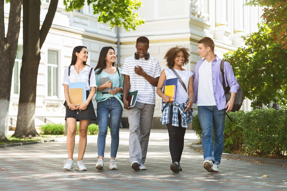 Group of multiethnic students walking together outdoors in college campus, holding books and notepads and laughing