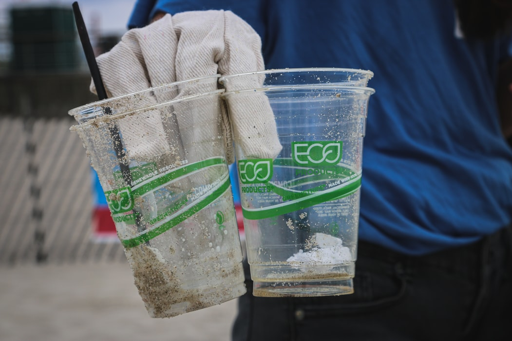 Close-up of a hand holding two plastic cups