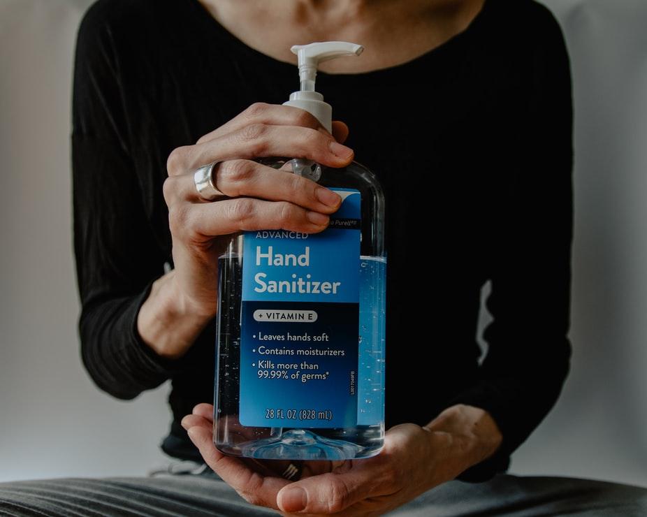 Hands holding a bottle of sanitizer