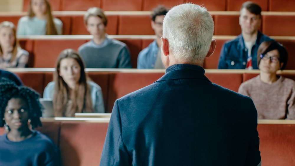 College professor gives a lecture to a classroom full of students