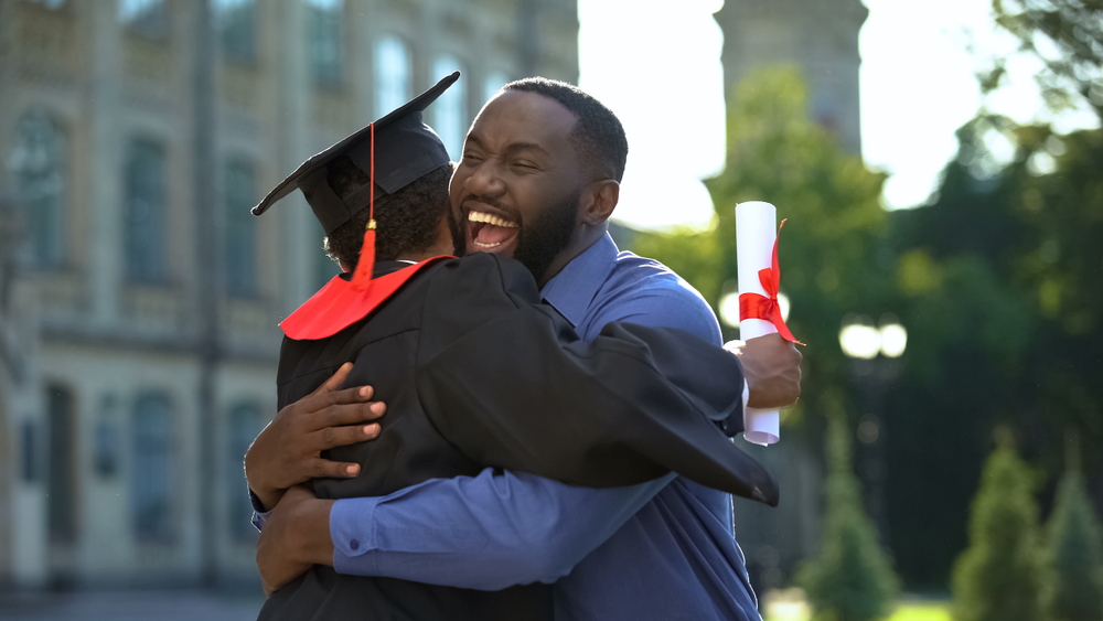 Cheerful father and graduating son hugging outdoor