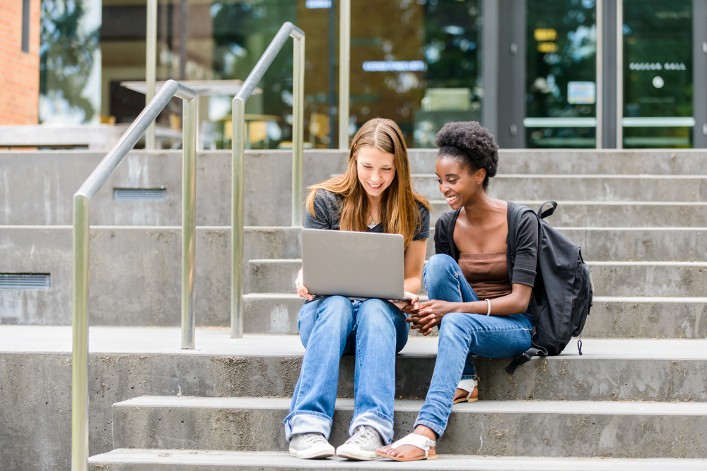 Female college students looking at a laptop, doing some work together on campus